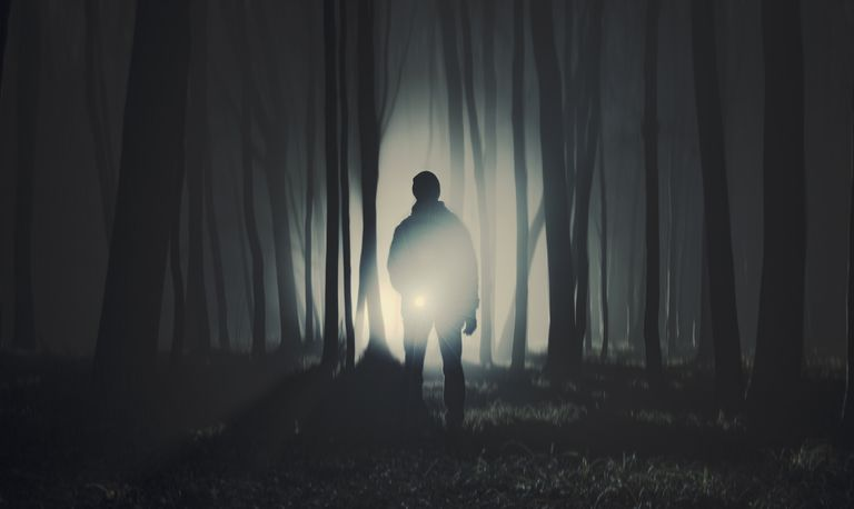 man in woods with flashlight