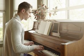 Young man playing the piano in living room