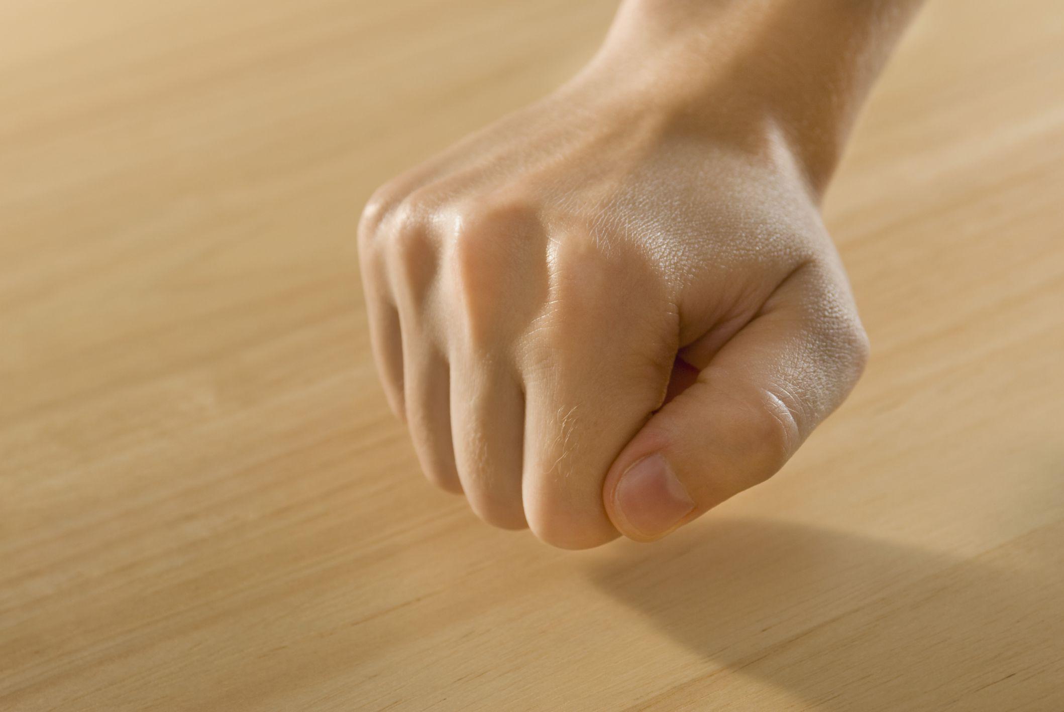 Image of a person knocking on wood.