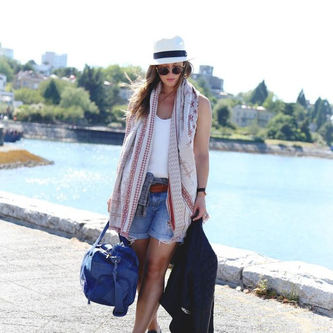 Woman in jean shorts and t-shirt with hat and summer scarf