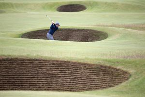 Paul Dunne, of Ireland, plays out of a bunker.