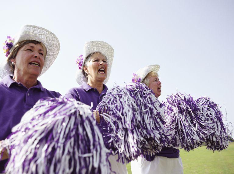 Three senior women in cheerleading uniforms with pom poms cheering