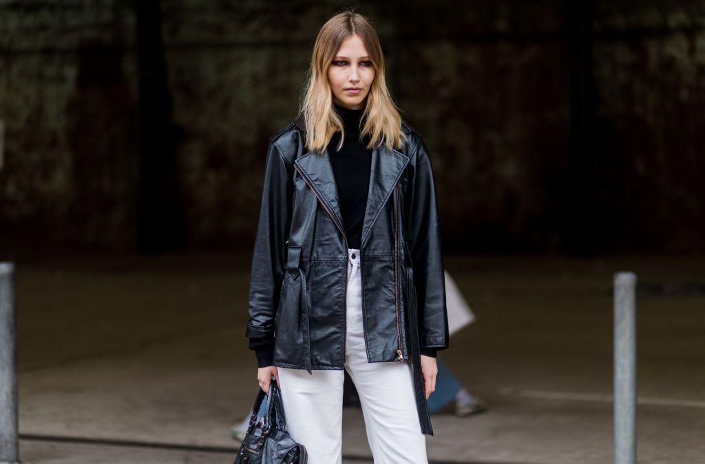 Woman wearing leather jacket and high waisted white jeans