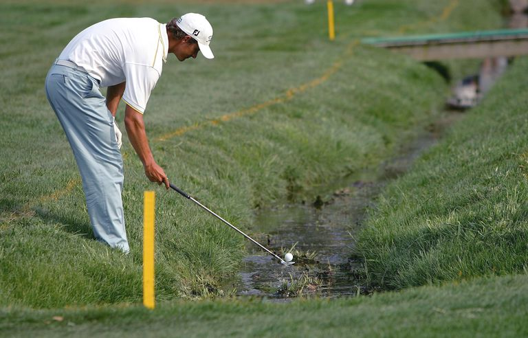 Yellow stakes indicate that Adam Scott is inside the boundary of a water hazard
