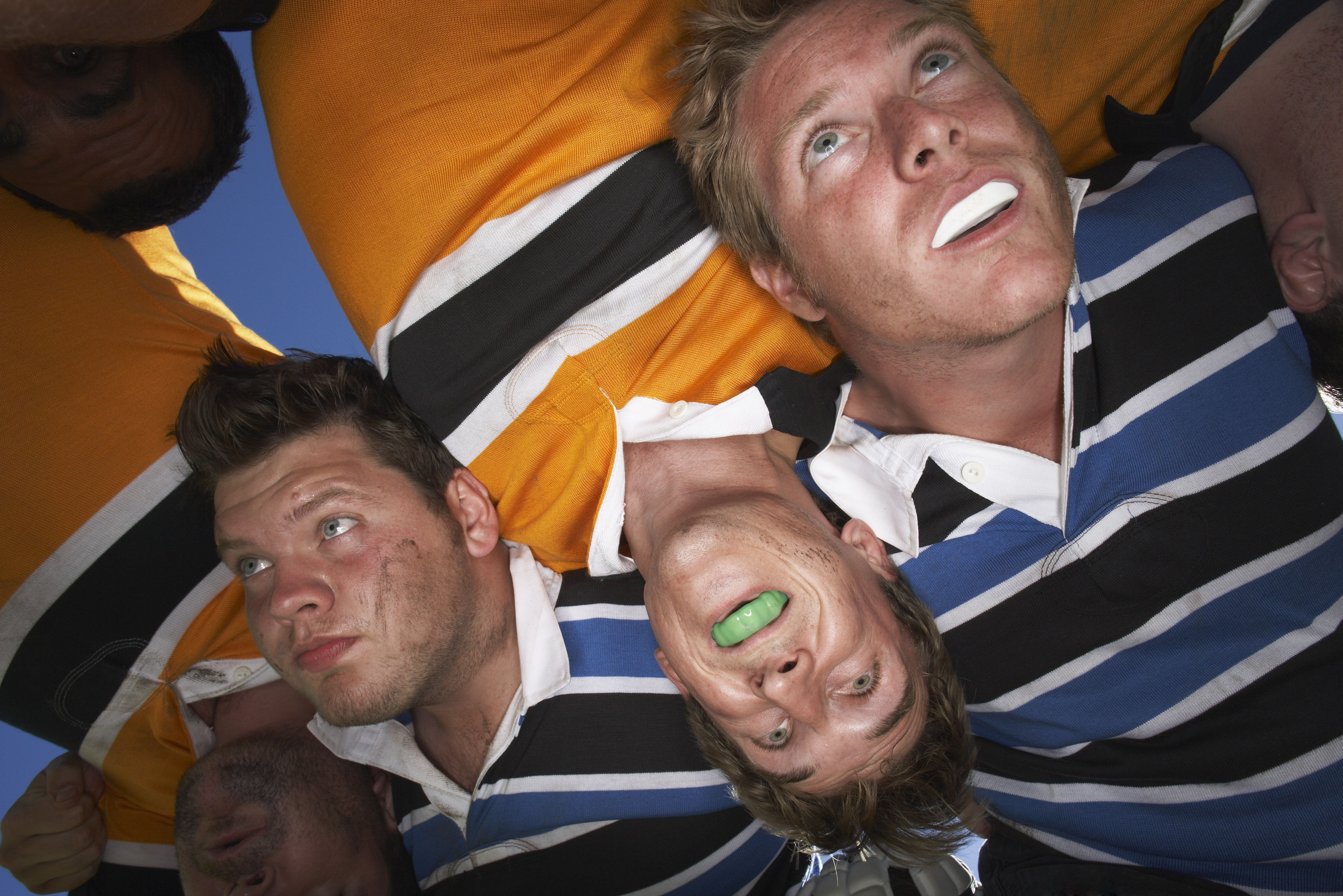 Rugby players with mouth guards huddling