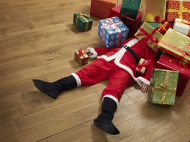 Santa Claus lying on the floor under a pile of presents.