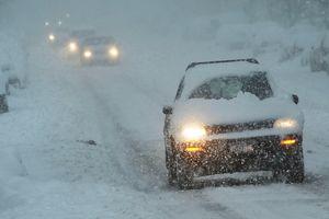 Cars drive through the snow