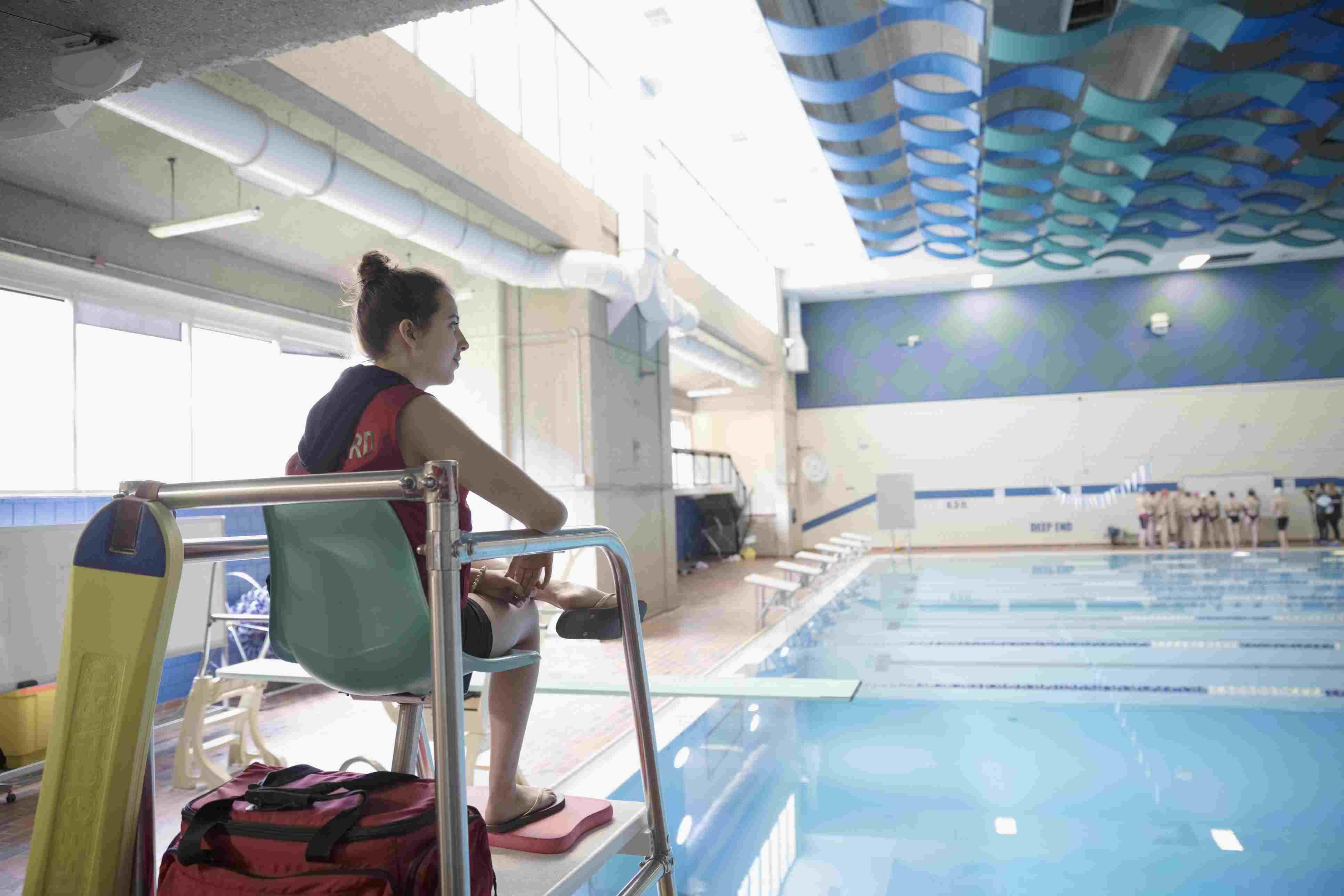 Female lifeguard sitting at lifeguard chair at swimming pool