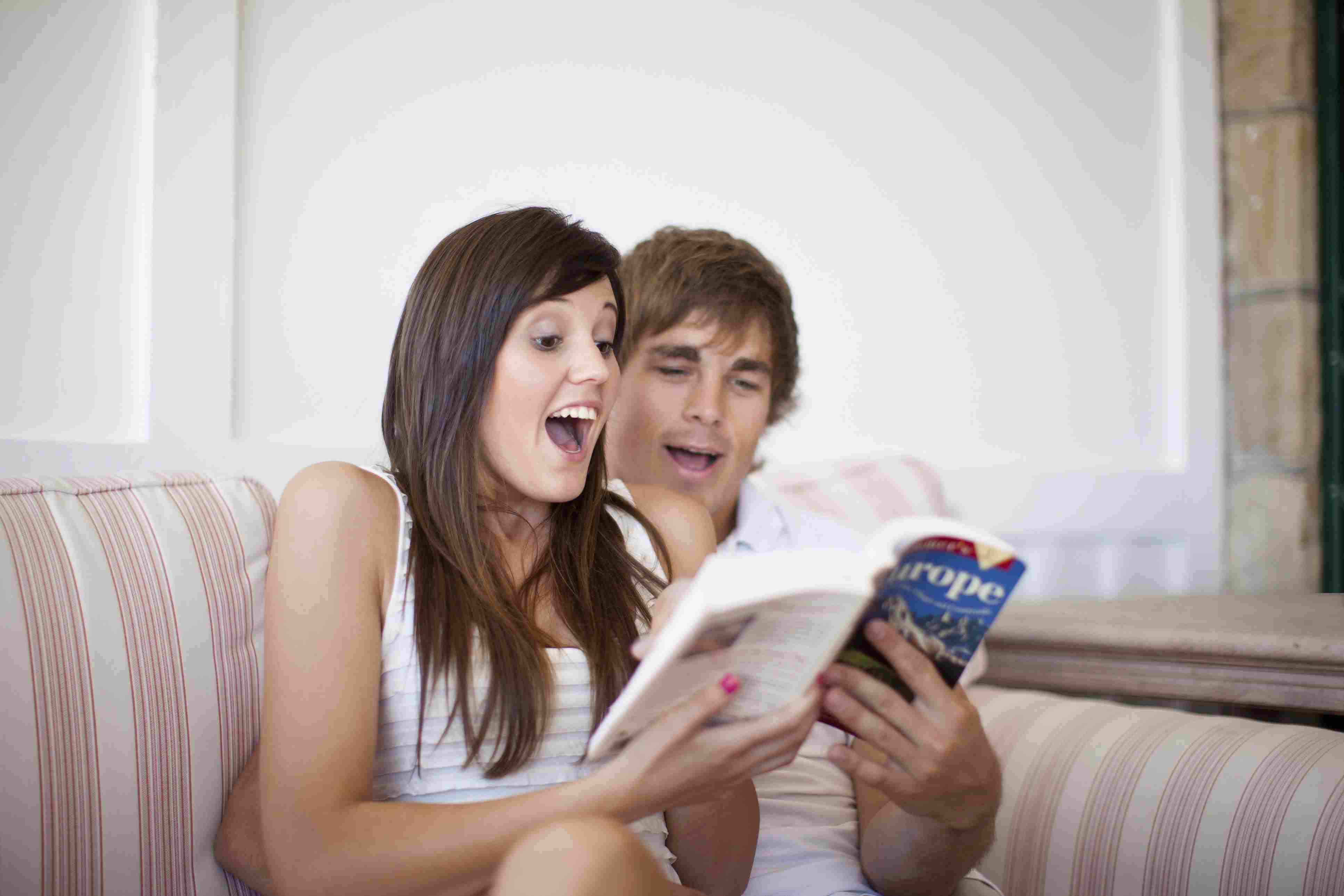 Couple reading travel book together