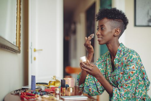 Woman applying cream to face in front of mirror