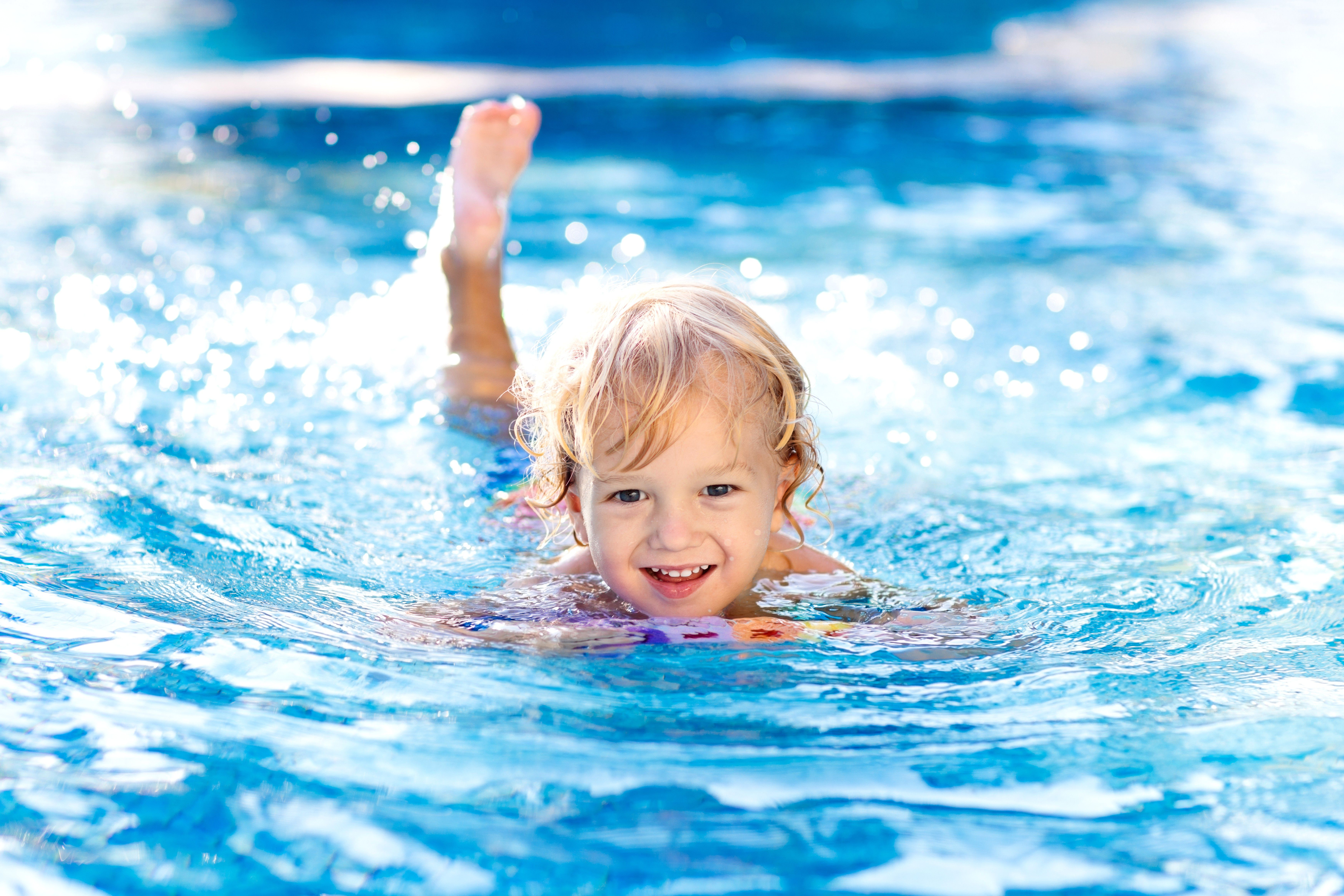 A small child learning to swim in a pool