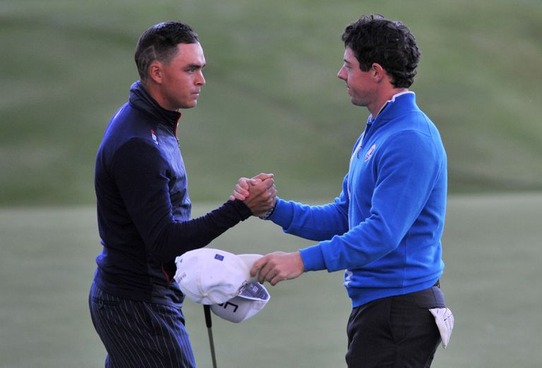 Rickie Fowler and Rory McIlroy shake hands following a tie in a Ryder Cup match.