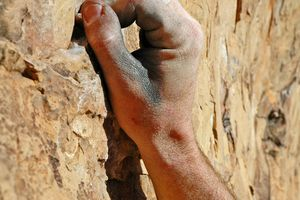 An arm using climbing handholds on a rock