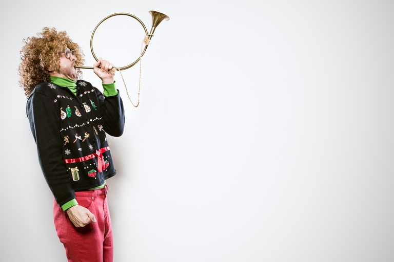 man in X-mas sweater playing trumpet