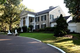 approaching a stone mansion with pillared portico and black shutters, curved driveway, sculptured steps