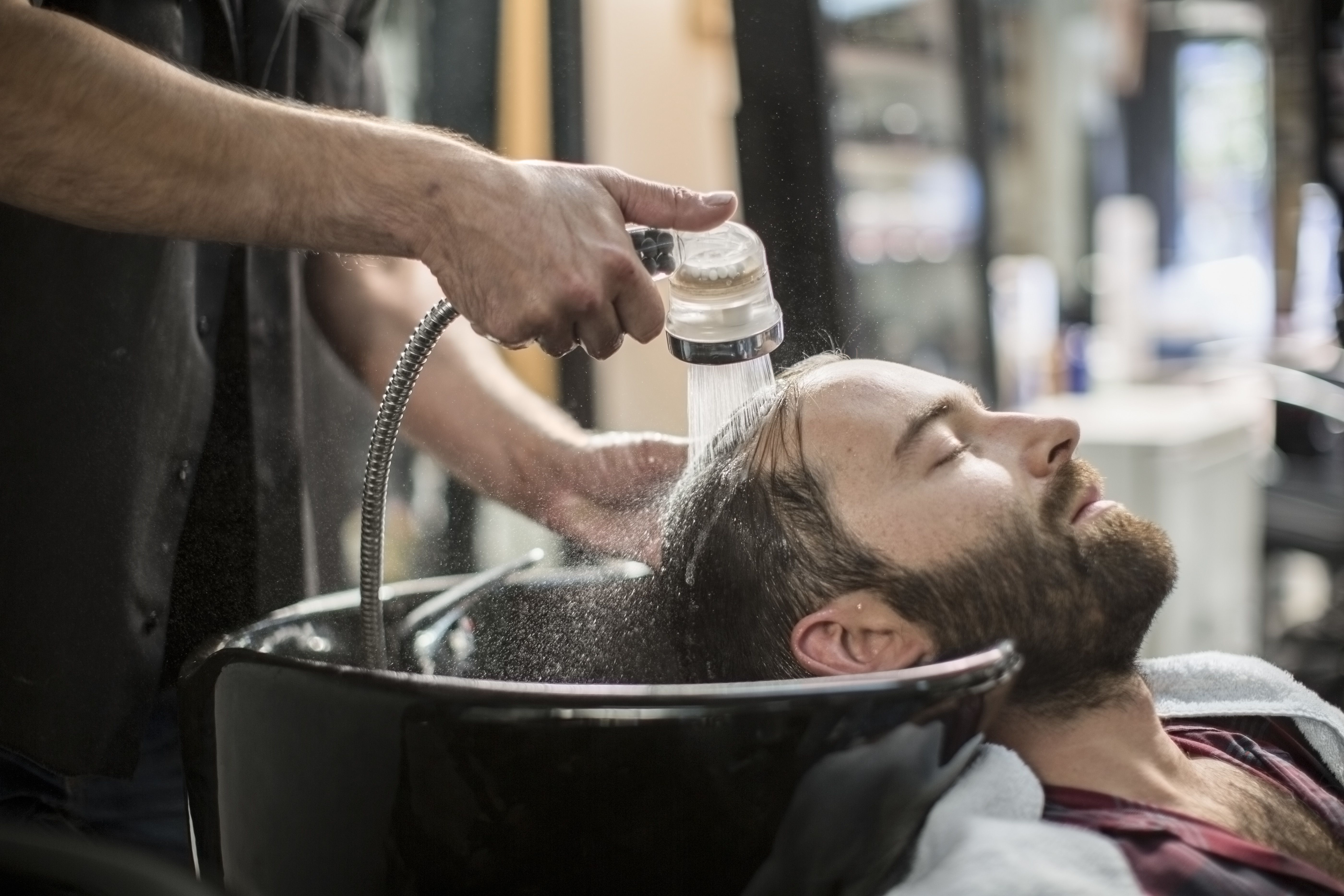 Customer laid back as he gets his hair washed