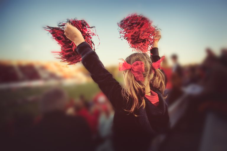 Little girl cheering at football game
