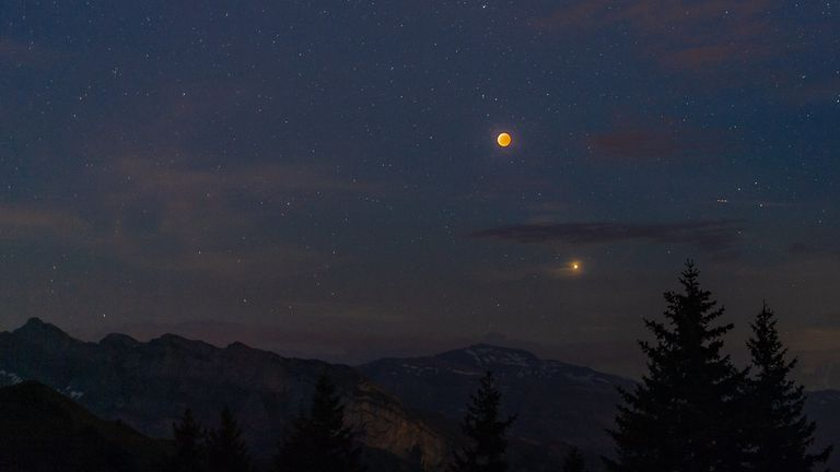 Mars and the moon both clearly visible in the night sky.