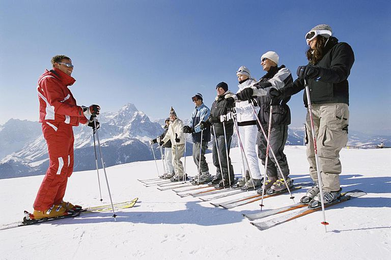 Ski Trainer With Men and Women on a ski Slope