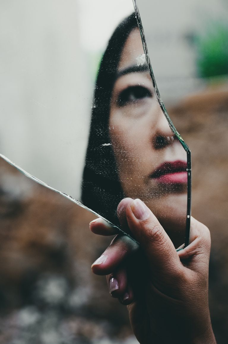 Woman reflected in broken mirror