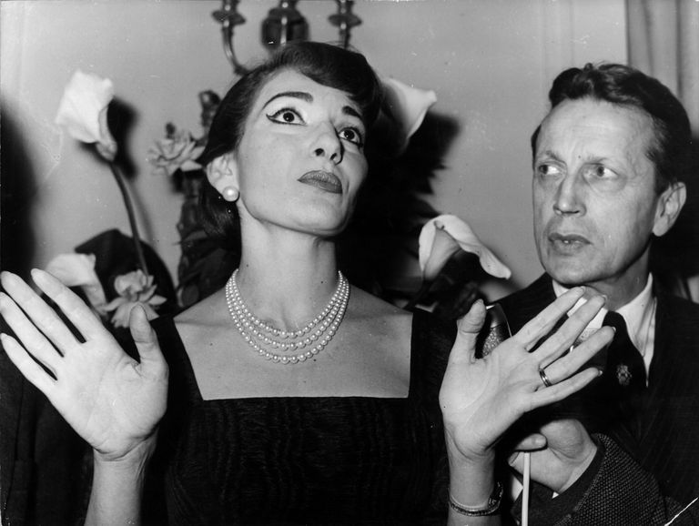 Soprano Maria Callas, known for her role as Carmen in Bizet's opera, Carmen, arrives in Paris for her first singing appearance in France at the Paris Opera. Monsieur Favre-Lebret is at her side as she addresses a press conference.