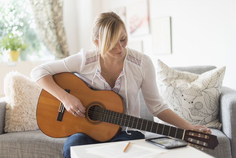 Woman sitting on sofa and playing acoustic guitar