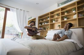 Enthusiastic man playing guitar for girlfriend on bed