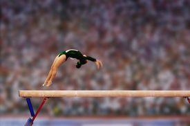 Female gymnast performing back flip on balance beam