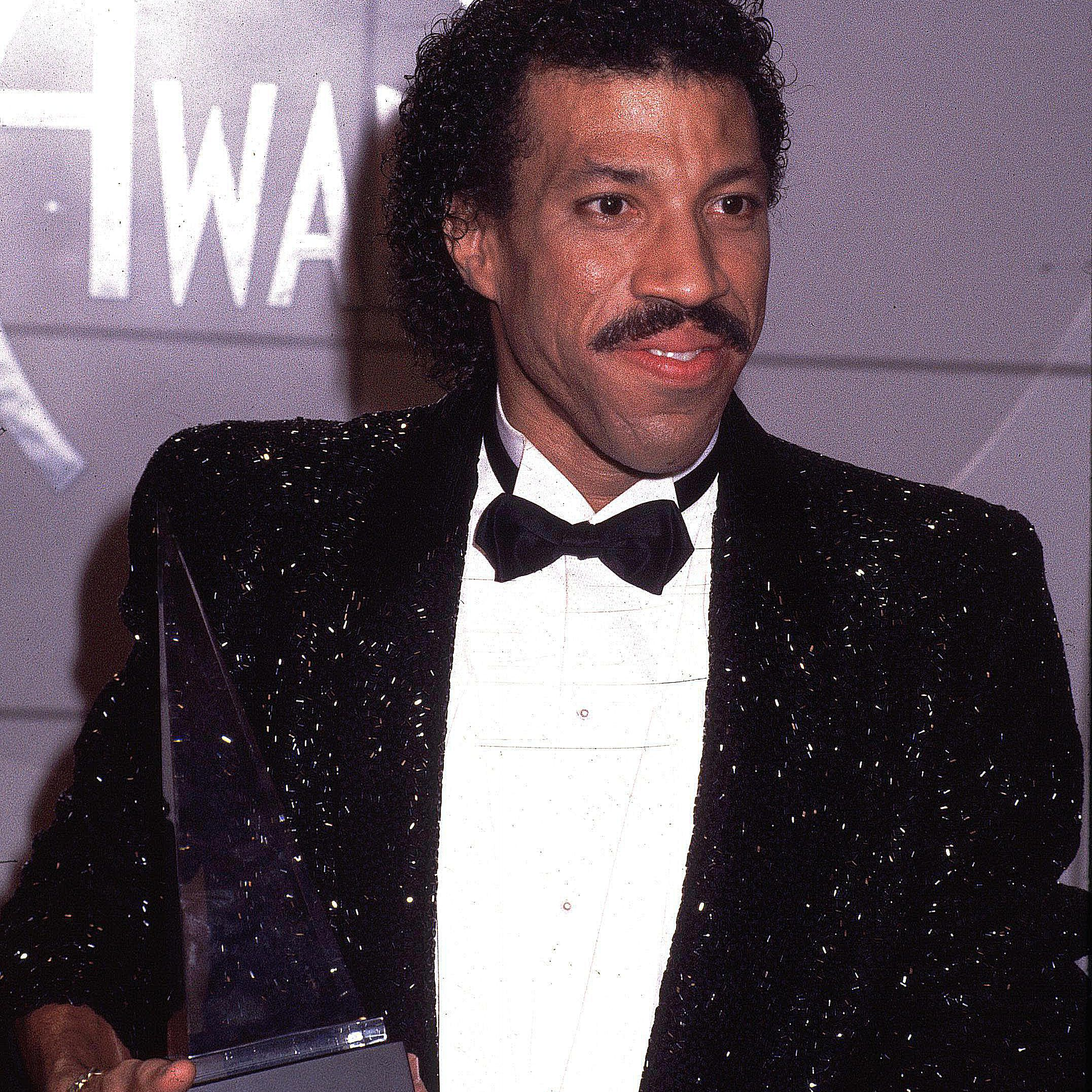 Lionel Richie posing with an award at the AMAs
