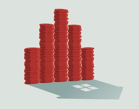 Stack of coins and shadow of house