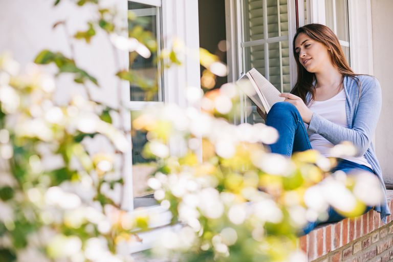 A woman, relaxing with a nice book in the country, is enjoying