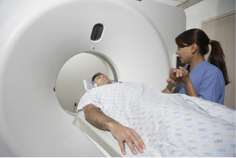 Indian nurse holding patient's hand in MRI scanner