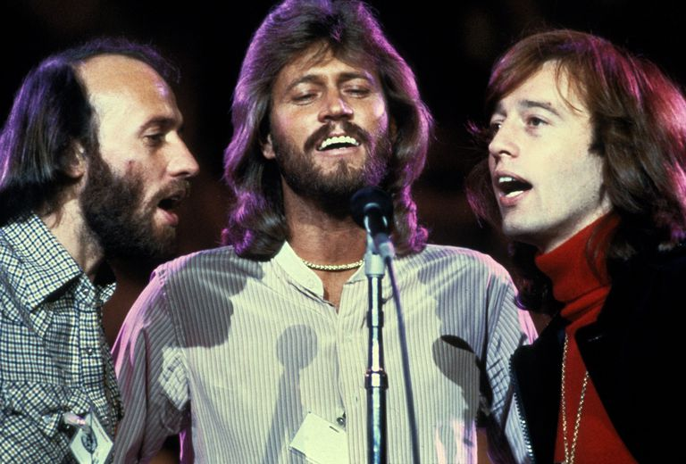 The Bee Gees singing at a microphone