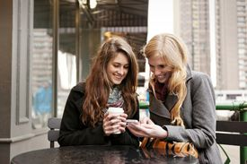 Smiling Young Women Looking At Cell Phone At Cafe