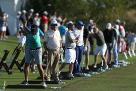 Golfers lined up on a driving range hitting balls