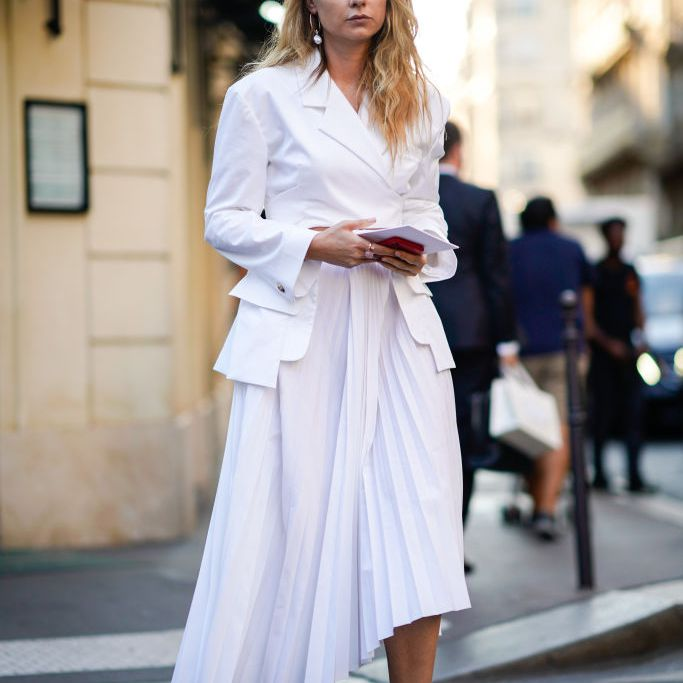 Woman in white jacket and white skirt