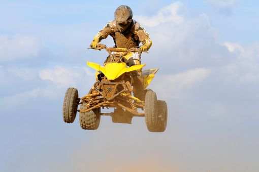 A dirty yellow quad flying over a jump