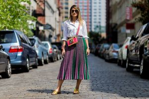 Street style woman wearing a pleated skirt and white blouse