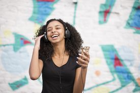 Teenager listening to mp3 player against wall with graffiti