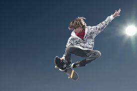 Teenage boy (16-17) performing jump on skateboard, low angle view