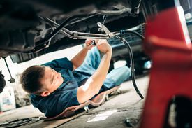 mechanic working under car supported by jack stands