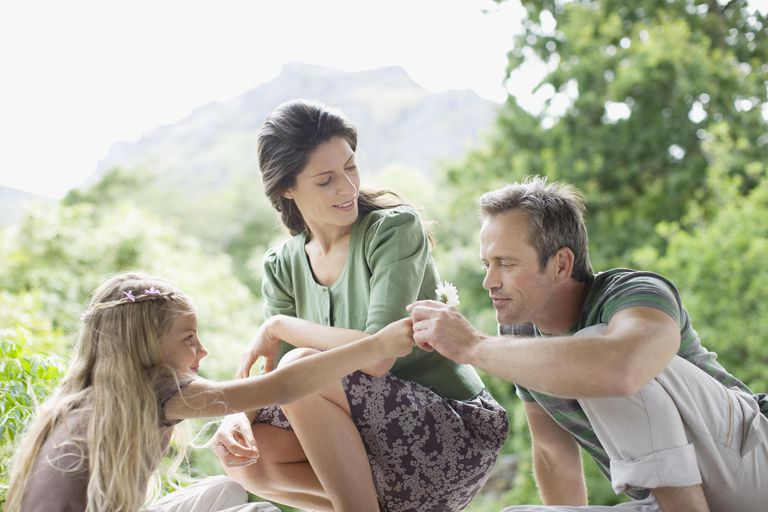 Girl handing father flower outdoors