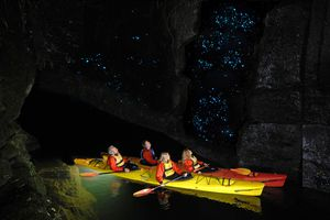 People kayaking through a cavern filled with glowworms.