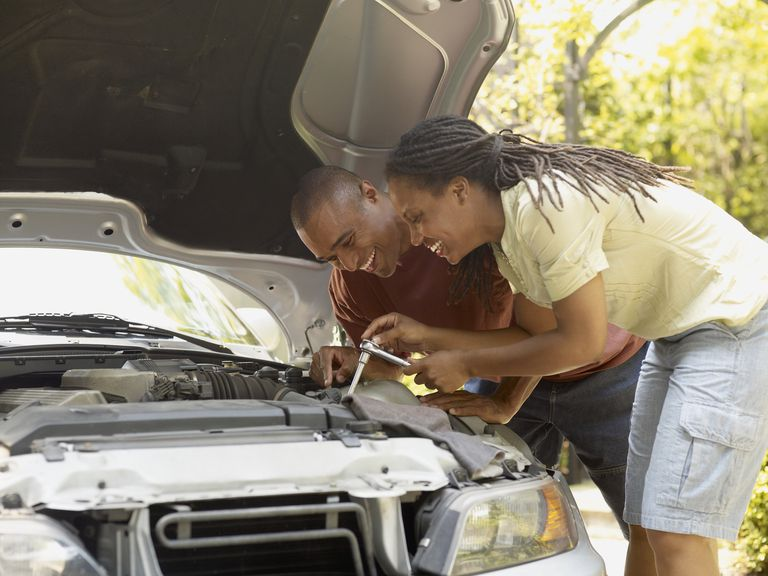 African couple working under hood of car
