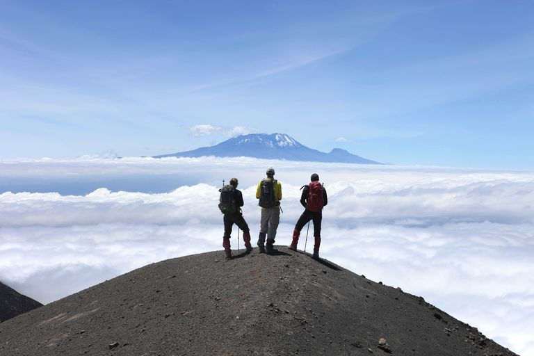 hikers are looking at Mount Kilimanjaro from the rocky ridge of Mount Meru.
