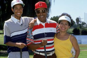 Tiger Woods, at age 14, posing with his mother and father Earl and Kultida Woods