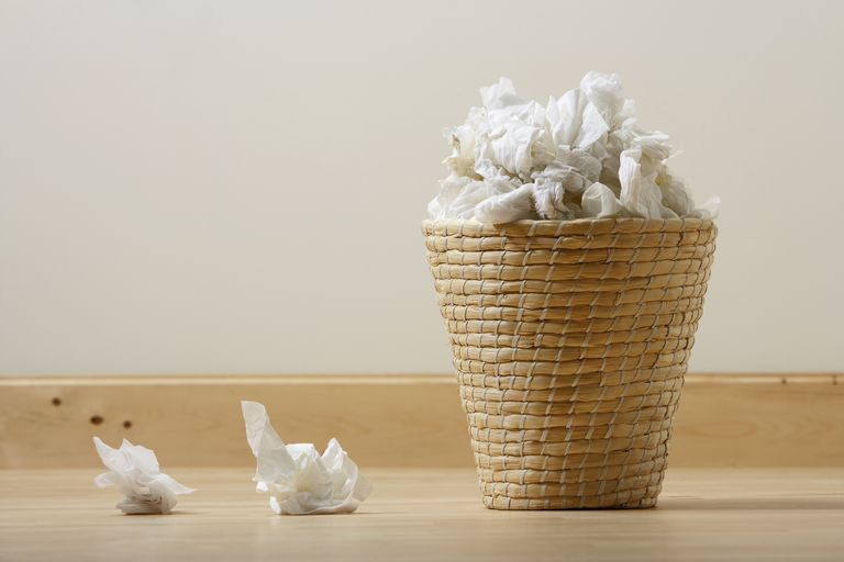 Waste basket overflowing with tissues.