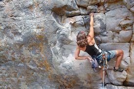 female rock climber scaling a rock face