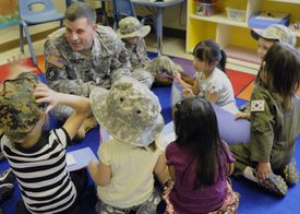 a soldier sitting on the floor and visiting with children