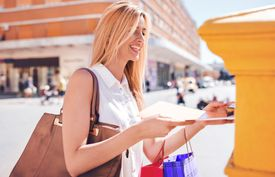 Young woman sending a folder and documents via mailbox. Business, lifestyle concept